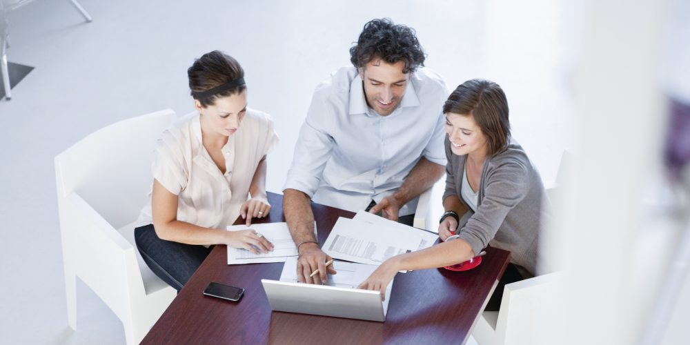 People at business meeting discussing documents and using laptop